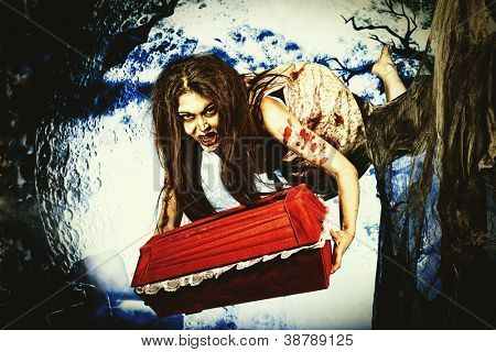 Bloodthirsty witch flying at the night cemetery with a coffin.