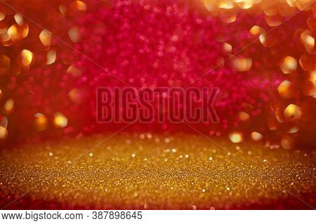 Gold And Red Abstract Glitter Background With Selective Focus. Red And Yellow Defocused Bokeh Lights