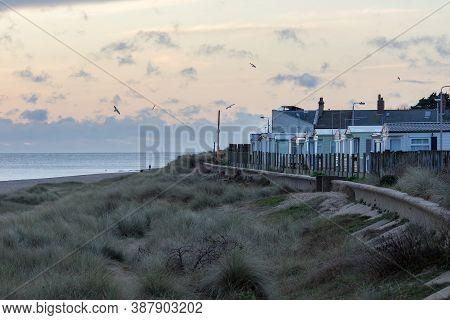 Seaside Vacation Homes In Winter. Coastal Retreat Norfolk Uk. Coastline Landscape With Beach Holiday