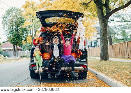 Trick Or Trunk. Children Celebrating Halloween In Trunk Of Car. Boy And Girl With Red Pumpkins Celeb