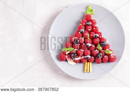 Christmas Food Art. Raspberry Berry Christmas Tree, Top View. Funny Idea For Child Festive Nutrition