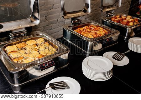 Silver Color Steam Table Of Delicious Portioned Hot Lasagne And Julienne In Bun And White Plate On B