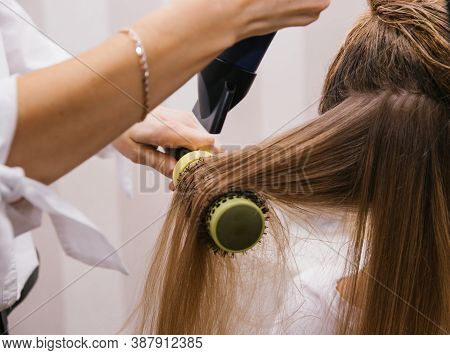 A Young Woman Dries Her Hair With A Hair Dryer. The Girl Combs Her Hair. Professional Hair Care Prod