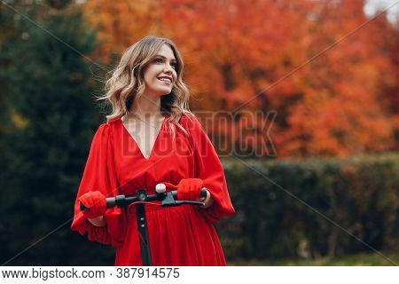 Young Woman Staying With Electric Scooter In Red Dress And Smile At The Autumn City Park