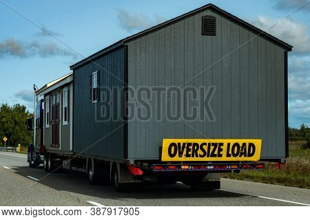 Two Pre-built Garden Sheds Are Being Transported By A Semi-trailer Transport Truck On A Highway, Wit