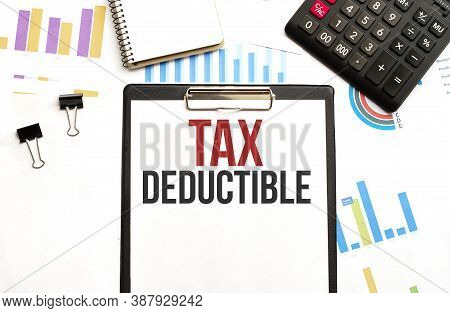 Paper Plate With Text Tax Deductible. Diagram, Calculator, Notepad And White Background