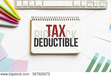 Businesman Hold Notepad With Text Tax Deductible. White Background. Business