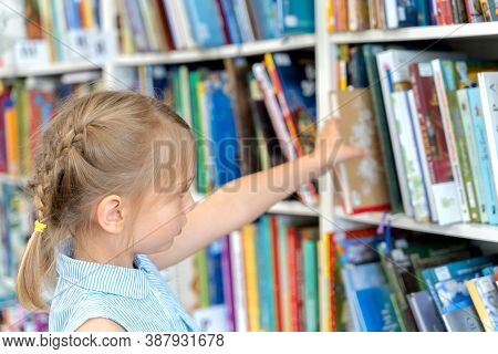 Little Girl Chooses, Takes Book With Fairy Tales From Shelf In Children's Library.special Reading Ki