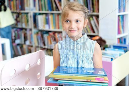 Little Girl Holds Stack Of Books With Fairy Tales In Children's Library. Special Reading Kids Room.