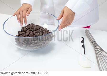 Female Chocolatier Keeps Dark Chocolate Couverture Callets In Glass Pot. Chocolate Drops For Prepara