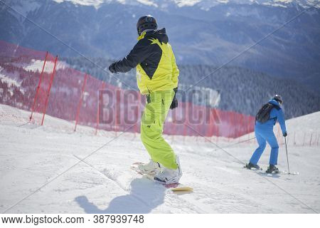 A Snowboarder Rides On A Slope. Rest On The Top Of The Mountain. Mountain Ski Resort. The Guy Is Rol