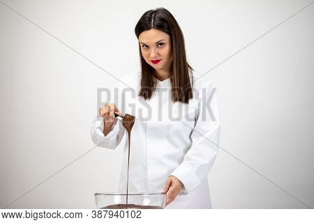 Beautiful Female Chocolatier Pouring Dark Melted Chocolate Isolated On White Background. Confectione