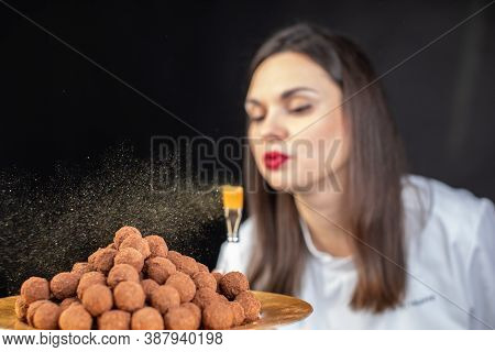 Attractive Female Confectioner Blows Gold Dust From Brush On Premium Handmade Truffles Isolated On B