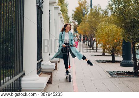Young Woman Ride Electric Scooter At The City Street