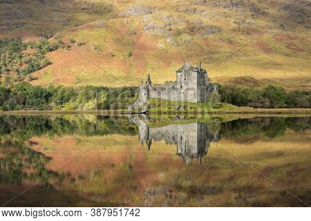 Kilchurn Castle In Scotland. Located On Loch Awe With Reflections In The Water And Autumn Colors