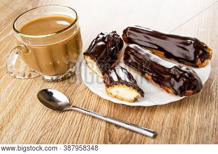 Transparent Cup Of Coffee With Milk, Two Whole Eclairs And Halves Of Eclair With Chocolate Glaze In