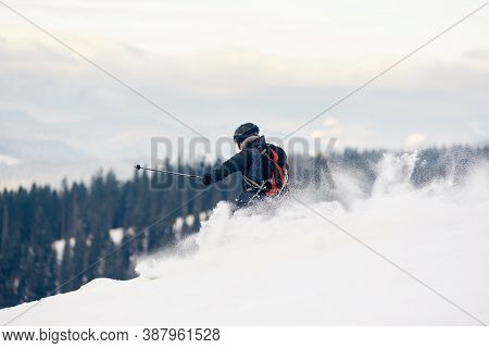 Back View Of Skier Backpacker Descending From Mountain In Deep White Snow Powder. Skier On High Slop