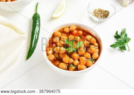 Close Up Of Indian Style Cooked Chickpeas In Bowl Over White Background. Vegetarian Vegan Food Conce