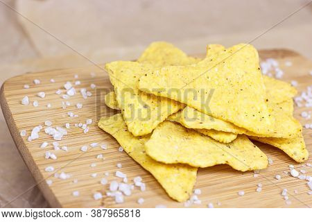 Salty Crunchy And Crispy Triangle Mexican Corn Nachos With Salt On Light Wooden Background.