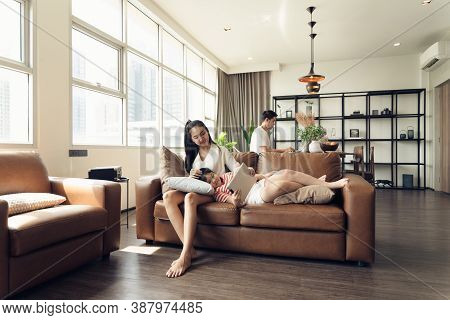 Asian Family Mother Father And Daughter Spending Time Together In The Living Room. Lifestyle Family