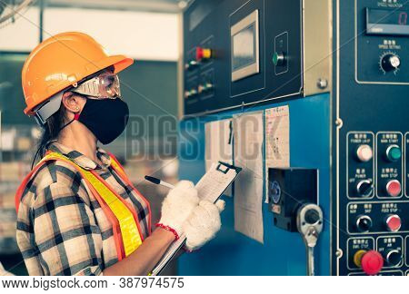 The Female Factory Inspector Wearing Face Mask And Safety Helmet With Eye Protective Holding Clipboa