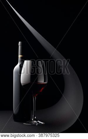 Bottle And Glass Of Red Wine On A Black Background. Copy Space.