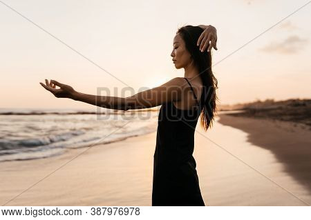 Freedom Chinese Woman Feeling Free Dancing In Black Elegant Dress At Beach Sunset. Healthy Living As