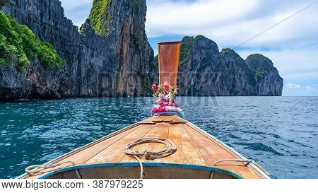 Traditional Wooden Longtail Boat Against Steep Limestone Hills In Phi Phi Island Krabi Province Thai