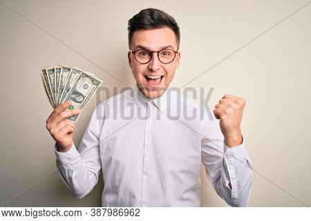 Young handsome caucasian business man holding bunch of one dollar banknotes screaming proud and celebrating victory and success very excited, cheering emotion