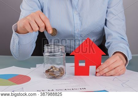 Woman Putting Coins Into Glass Jar Near Model House. Woman Hand Putting A Coin Into A Jar Bank On De
