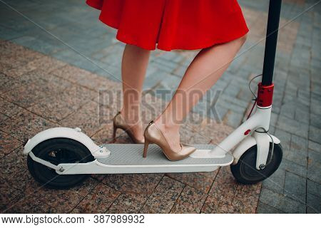 Legs Of Woman With Electric Scooter In Red Dress At The City