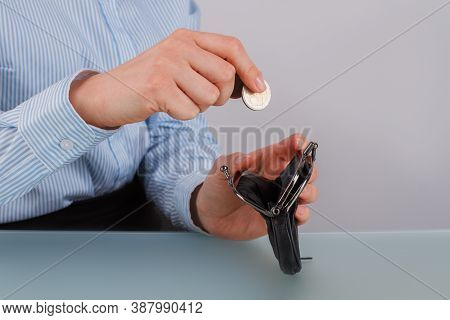 Female Hand Putting Coin Into Purse. Business Woman Puts Coin Into Black Wallet. Savings Concept.
