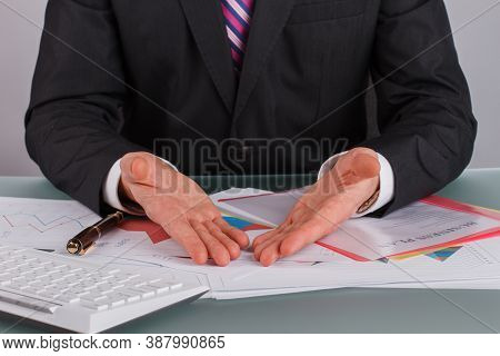 Close Up Businessman Analyzing Data At Desk In Office. Financial Inspector Analyzing Sales Documents