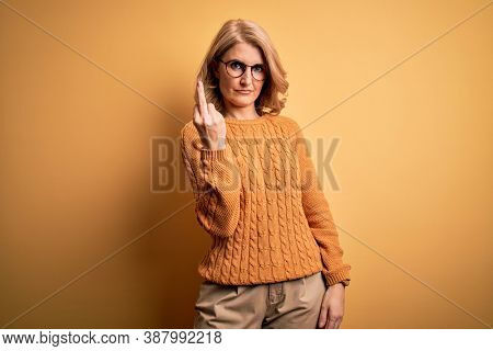 Middle age beautiful blonde woman wearing casual sweater and glasses over yellow background Showing middle finger, impolite and rude fuck off expression