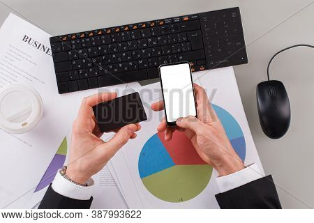 Male Hands Holding Business Card And Mobile Phone In Office. Business Man Hands Using Computer, Smar