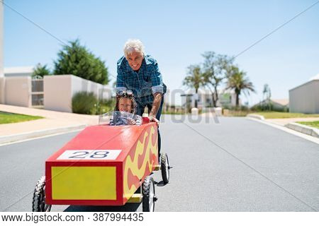 Grandfather helping grandson ride on kids toy car with copy space. Senior man pushing go-kart with boy riding it with pilot helmet. Old grandpa playing with grandchild ride toy car.