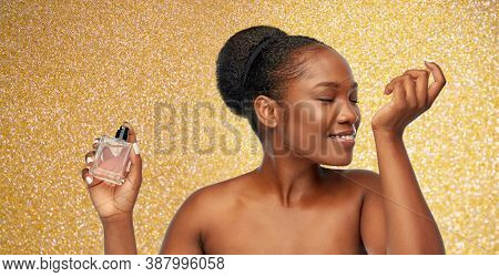 beauty, luxury and perfumery concept - portrait of happy smiling young african american woman with bare shoulders smelling perfume over golden glitter on background