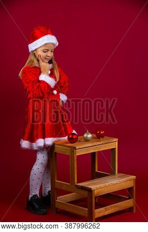 Little Girl With Blond Hair, Having Hard Times Choosing Xmas Tree Decoration, Happy New Year, Red Is