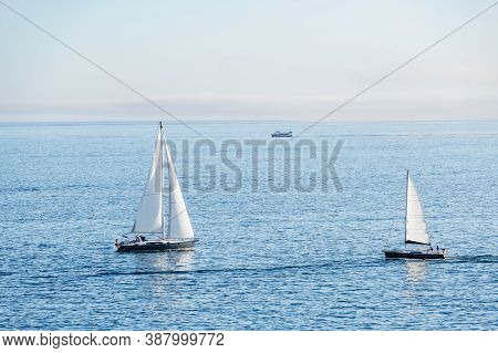 Two Sailboats And A Ferry Enter And Depart From The Ria De Pontevedra In Galicia At Dusk.