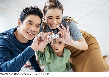 Happy Family, Asian Little Daughter Playing Jigsaw Puzzle With Her Mother And Father For Family Conc