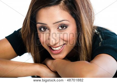 Close-up portrait of fresh, beautiful young Asian Indian model, head resting on arms and desk.