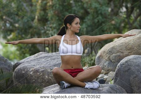 Full length of a fit young woman sitting on stone with arms out in park poster