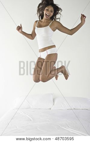 Full length of an excited young woman jumping on bed