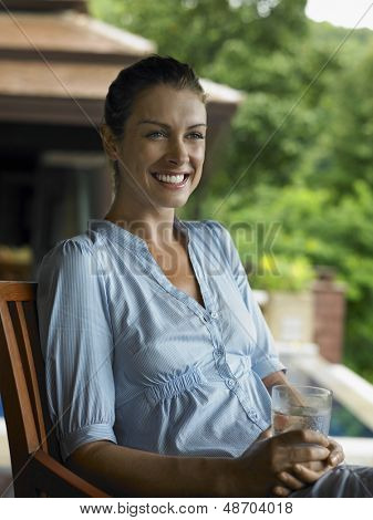 Smiling young woman sitting with a glass of water in veranda