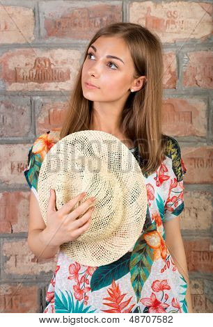 Portrait Of Pensive Girl With A Straw Hat In Hand.