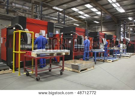 Rear view of workers at manufacture workshop operating machines