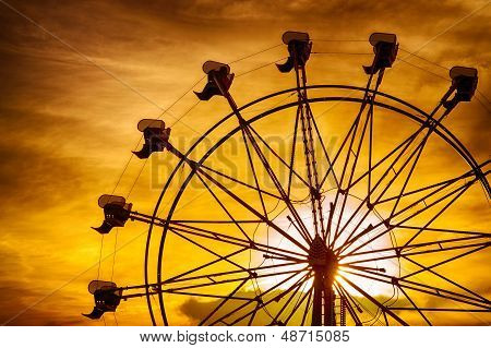 Silhouette of ferris wheel at sunset during summer at county fair