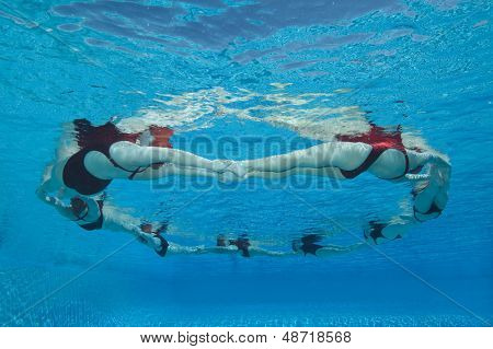 Underwater view of synchronized swimmers forming a circle in pool