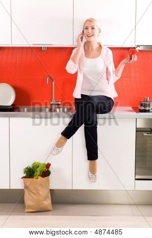 Woman Sitting On Kitchen Counter