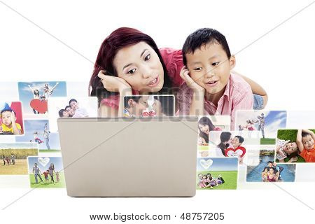 Cute Mother And Son Looking At Photos On Laptop